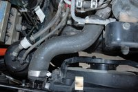 25. Position catch pan under hose.  Remove the top coolant hose from radiator.